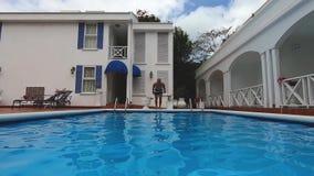 Άλματα νεαρών άνδρων στο μπλε νερό στην πισίνα GoPro Hero7 φιλμ μικρού μήκους
