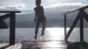 Άλματα παιδιών από μια ξύλινη αποβάθρα στο νερό απόθεμα βίντεο