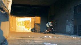 Άλματα ποδηλατών σε ένα κτήριο, που κάνει τις ακροβατικές επιδείξεις, σε αργή κίνηση φιλμ μικρού μήκους