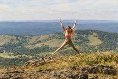 Άλμα κοριτσιών υψηλό στα βουνά, μπλε ουρανός, θερινό τοπίο Στοκ εικόνα με δικαίωμα ελεύθερης χρήσης