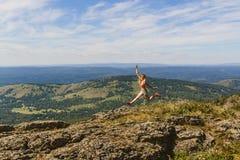 Άλμα κοριτσιών υψηλό στα βουνά Στοκ Φωτογραφίες