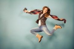 Άλμα κοριτσιών φθινοπώρου μόδας γυναικών, που πετά στον αέρα στο μπλε Στοκ Εικόνες