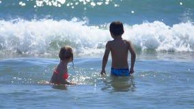 Άλμα μικρών παιδιών και κοριτσιών στα κύματα φιλμ μικρού μήκους