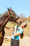 Άλογο κάστανων που φιλά τη νέα γυναίκα ιδιοκτητών της ιππική Στοκ εικόνα με δικαίωμα ελεύθερης χρήσης