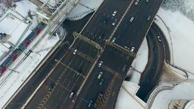 Άμεσα ανωτέρω - αυτοκίνητα και τραίνο που κινούνται σε έναν δρόμο, γέφυρα το χειμώνα Τοπ άποψη από το copter απόθεμα βίντεο