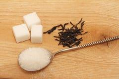 Άμμος ζάχαρης σε ένα ασημένιο κουτάλι και σε ένα ξύλινο υπόβαθρο Στοκ Φωτογραφία