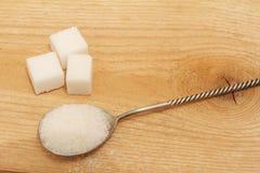 Άμμος ζάχαρης σε ένα ασημένιο κουτάλι και σε ένα ξύλινο υπόβαθρο Στοκ Φωτογραφίες
