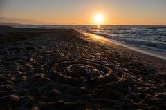 Άμμος και ήλιος όμορφο νεφελώδες ύδωρ ουρανού θάλασσας βράχων αυγής Στοκ Φωτογραφίες