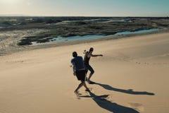 άμμος νεαρών άνδρων δύο που επιβιβάζεται στους αμμόλοφους άμμου ερήμων κοντά στην πόλη στοκ εικόνα με δικαίωμα ελεύθερης χρήσης