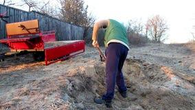 Άμμος φορτίων ατόμων με ένα φτυάρι στο ρυμουλκό του motoblock απόθεμα βίντεο
