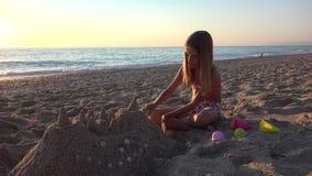 Άμμος Castle παιχνιδιού παιδιών στην παραλία στο ηλιοβασίλεμα, κορίτσι στην ακτή, ακτή 4K απόθεμα βίντεο
