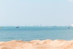 Άμμος seaview και πόλη στο υπόβαθρο Στοκ Εικόνες