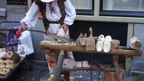 Άμστερνταμ, Κάτω Χώρες - 14 Ιουνίου 2017: Ο handicraftsman παράγει τα παραδοσιακά ξύλινα υποδήματα klomp στην οδό απόθεμα βίντεο