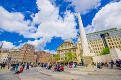 Άμστερνταμ, Κάτω Χώρες - 10 Ιουλίου 2015: Τετράγωνο φραγμάτων μια όμορφη ηλιόλουστη ημέρα, ένα ψηλό μνημείο και ιστορικά κτήρια Στοκ εικόνα με δικαίωμα ελεύθερης χρήσης
