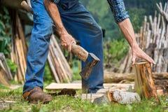 Άνδρας εργαζόμενος με το ξύλινο τεμαχίζοντας καυσόξυλο τσεκουριών Στοκ Εικόνα