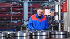 Άνδρας εργαζόμενος μπλε σε ομοιόμορφο στη συμπεριφορά του εργοστασίου Ο μηχανικός συγκεντρώνει τα ρουλεμάν, έννοια βιομηχανίας Έν απόθεμα βίντεο