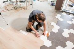 Άνδρας εργαζόμενος που εγκαθιστά το νέο ξύλινο φυλλόμορφο δάπεδο Ο συνδυασμός ξύλινων επιτροπών των φυλλόμορφων και κεραμικών κερ στοκ φωτογραφία