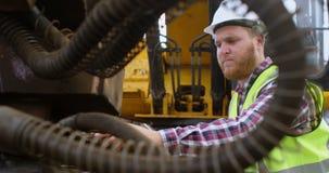 Άνδρας εργαζόμενος που εξετάζει τη μηχανή 4k απόθεμα βίντεο