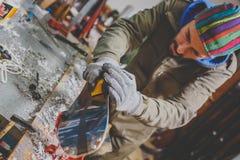 Άνδρας εργαζόμενος που επισκευάζει το Stone, ακόνισμα ακρών στο εργαστήριο υπηρεσιών σκι, επιφάνεια ολίσθησης των σκι ακόνισμα εν στοκ φωτογραφία