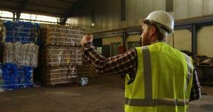 Άνδρας εργαζόμενος που εργάζεται στην αποθήκη εμπορευμάτων 4k απόθεμα βίντεο