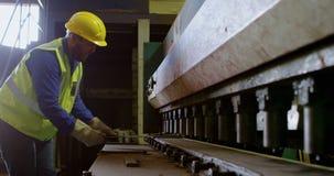 Άνδρας εργαζόμενος που εργάζεται στη μηχανή στην αποθήκη εμπορευμάτων 4k απόθεμα βίντεο