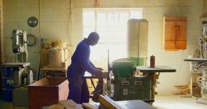 Άνδρας εργαζόμενος που κόβει τον ξύλινο φραγμό στο εργαστήριο 4k απόθεμα βίντεο