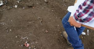 Άνδρας εργαζόμενος που περπατά με την περιοχή αποκομμάτων στο junkyard 4k απόθεμα βίντεο