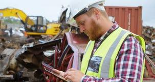 Άνδρας εργαζόμενος που χρησιμοποιεί την ψηφιακή ταμπλέτα στο junkyard 4k φιλμ μικρού μήκους