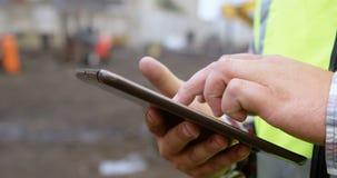 Άνδρας εργαζόμενος που χρησιμοποιεί την ψηφιακή ταμπλέτα στο junkyard 4k απόθεμα βίντεο