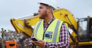 Άνδρας εργαζόμενος που χρησιμοποιεί το κινητό τηλέφωνο στο junkyard 4k απόθεμα βίντεο