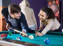 Άνδρας και ένα νέο ζεύγος μπιλιάρδου γυναικών παίζοντας που εξετάζει κάθε ο στοκ φωτογραφία