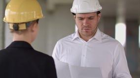 Άνδρας και γυναίκα επιχειρηματιών που συζητούν για την οικοδόμηση του σχεδίου για την κατασκευή επί του τόπου εργασίας απόθεμα βίντεο