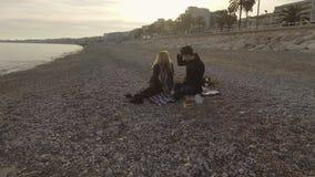 Άνδρας και γυναίκα ερωτευμένοι έχοντας το πικ-νίκ από την παραλία, που ανοίγει το μπουκάλι του κρασιού, ημερομηνία απόθεμα βίντεο