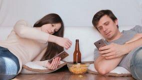 Άνδρας και γυναίκα ζεύγους που κοιτάζουν βιαστικά Διαδίκτυο στα κινητά τηλέφωνά τους που πίνουν την μπύρα και που τρώνε τα τσιπ απόθεμα βίντεο