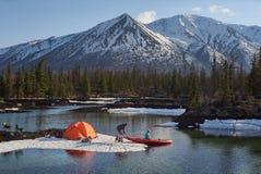 Άνδρας και γυναίκα ζεύγους σε ένα στρατόπεδο στην έκταση βουνών Ακτή λιμνών με το κανό στοκ εικόνες με δικαίωμα ελεύθερης χρήσης