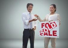 Άνδρας και γυναίκα με για το σημάδι και τα κλειδιά πώλησης μπροστά από το σύντομο χρονογράφημα Στοκ φωτογραφία με δικαίωμα ελεύθερης χρήσης