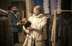 Άνδρας και γυναίκα με τα παλτά στο κατάστημα γουνών στοκ εικόνες με δικαίωμα ελεύθερης χρήσης