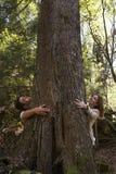 Άνδρας και γυναίκα που αγκαλιάζουν ένα δέντρο Στοκ Φωτογραφίες