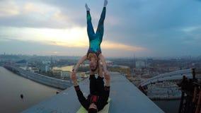 Άνδρας και γυναίκα που ασκούν την ακροβατική γιόγκα πάνω από τη γέφυρα, επικίνδυνος αθλητισμός απόθεμα βίντεο