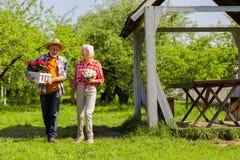 Άνδρας και γυναίκα που γελούν μετά από να φυτεψει τα λουλούδια στα δοχεία από κοινού στοκ φωτογραφία με δικαίωμα ελεύθερης χρήσης