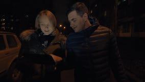 Άνδρας και γυναίκα που διοργανώνουν μια συζήτηση κατά την περπάτημα το χειμερινό βράδυ φιλμ μικρού μήκους