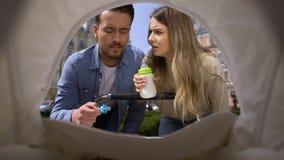 Άνδρας και γυναίκα που εξετάζουν το νήπιο στη μεταφορά, ανησυχημένοι νέοι γονείς, προσοχή απόθεμα βίντεο
