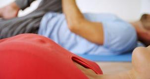Άνδρας και γυναίκα που κάνουν την τεντώνοντας άσκηση ποδιών στο στούντιο ικανότητας 4k απόθεμα βίντεο