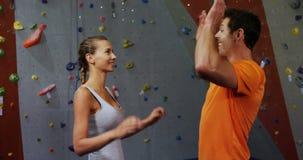 Άνδρας και γυναίκα που μιλούν και που δίνουν υψηλός-πέντε ο ένας στον άλλο 4k απόθεμα βίντεο