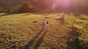 Άνδρας και γυναίκα που περπατούν στο ηλιοβασίλεμα απόθεμα βίντεο