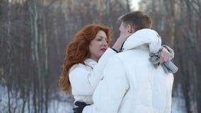Άνδρας και γυναίκα που στέκονται στο χειμερινό πάρκο φιλμ μικρού μήκους