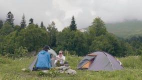 Άνδρας και γυναίκα που στηρίζονται στη σκηνή στρατοπέδευσης και το υπόβαθρο τοπίων βουνών φιλμ μικρού μήκους