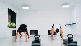 Άνδρας και γυναίκα σε ένα στούντιο ικανότητας που κάνει τα άλματα επίτόπου απόθεμα βίντεο