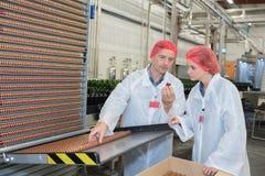 Άνδρας και γυναίκα στα άσπρα παλτά που λειτουργούν στο εργοστάσιο Στοκ φωτογραφία με δικαίωμα ελεύθερης χρήσης