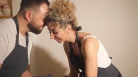 Άνδρας και γυναίκα στην ποδιά που φιλά και που ρίχνει το δοχείο στην περιστροφή της ρόδας αγγειοπλαστικής απόθεμα βίντεο